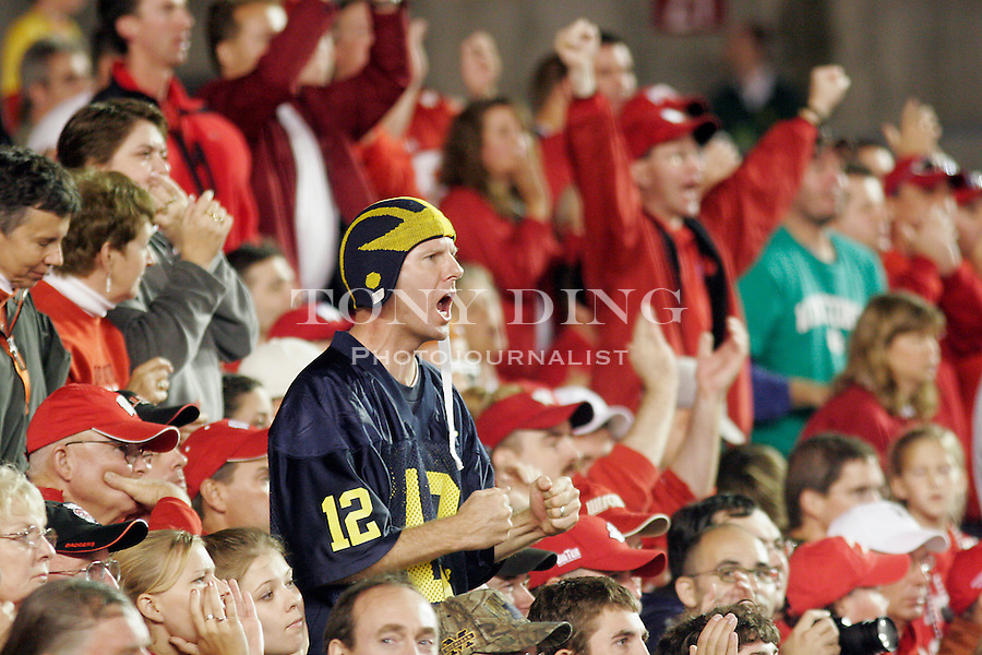 24 Sep 2005: A Michigan fan wearing a retro mock helmet cheers on the Wolverines amongst Badger fans during the Wisconsin Badgers 23-20 win over the Michigan Wolverines at Camp Randall Stadium in Madison, Wisconsin. This is the Badgers' first victory over Michigan since 1994 and it ends a 23 year Big Ten opener win streak for the Wolverines.