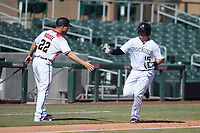 Salt River Rafters first baseman Brian Mundell (15), of the Colorado Rockies organization, is congratulated by manager J.R. House (22) after hitting a home run off Kyle McGowin (not pictured) during an Arizona Fall League game against the Mesa Solar Sox on October 30, 2017 at Salt River Fields at Talking Stick in Scottsdale, Arizona. The Solar Sox defeated the Rafters 8-4. (Zachary Lucy/Four Seam Images)