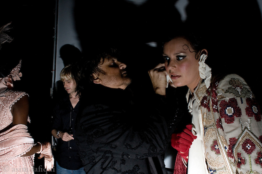 Pakistan's best known fashion designer Rizwan Beyg (center) prepares a model before she walks onto the catwalk at a fashion show in Dubai.  Pakistani entrepreneurs and businessmen increasingly consider the cities of London, Dubai and even Bombay as crucial markets for their products and services and frequently travel and offer their products there.