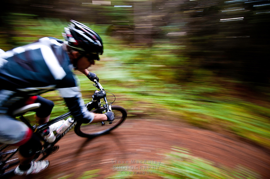 Motion blur shot of male mountain biker speeding around a turn, Galbraith Mountain, Bellingham WA.