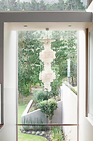 This contemporary chandelier hangs in the stairwell just off the study. The full height window gives a view of the garden.