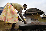 In a camp for families displaced by internal conflict in northern Uganda, Covia Akwi cooks grain that will be turned into home brew. The two-decade conflict began winding down with peace talks in 2006, and some displaced families have returned home.
