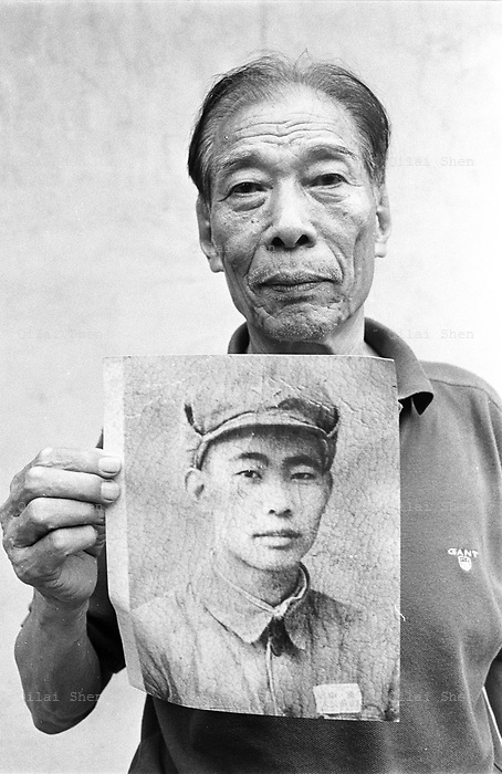 A man holding a picture taken prior to the Korean War. He was later captured by the Americans and voluntarily moved to Taiwan.
