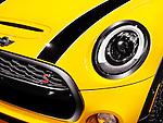 Yellow 2014 Mini Cooper S closeup of car detail, headlight and hood
