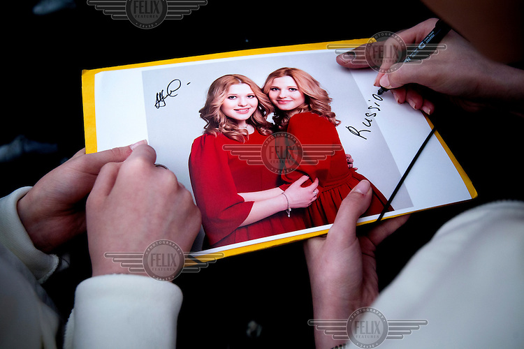 Behind the scenes at Eurovision 2014. Russia's Tolmachchevy Sisters, who sang 'Shine' during the show, autographing a publicity still for a fan.
