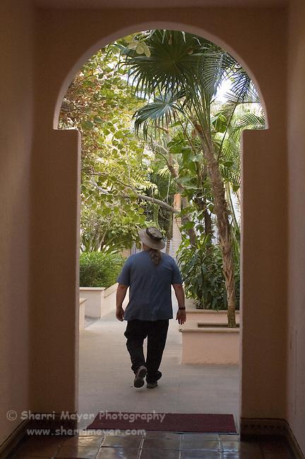 Tourist walking through the garden at the Pueblo Bonito Rose Resort, Cabo San Lucas, Baja California, Mexico