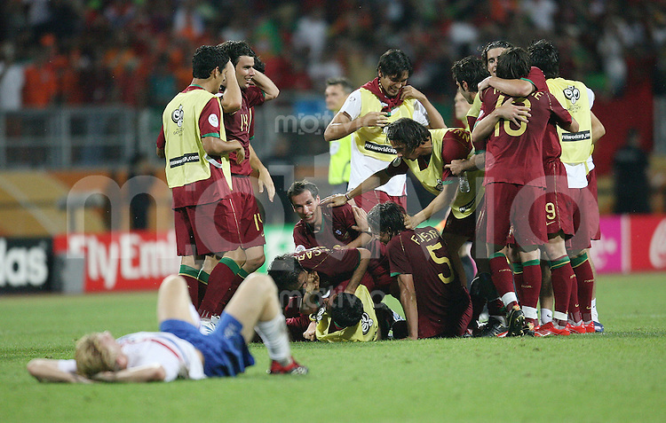 Fussball WM 2006 Achtelfinale  Portugal - Niederlande  Die Portugiesischen Spieler jubeln nach dem Spiel ueber den Sieg waehrend Dirk Kuyt (NED vorne) enttaeuscht am Boden liegt