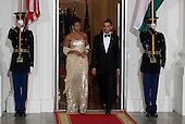 Washington, DC - November 24, 2009 -- United States President Barack Obama, right, and U.S. First Lady Michele Obama arrive to greet Manmohan Singh, India's prime minister, and his wife Gursharan Kaur at the White House in Washington, D.C., U.S., on Tuesday, November 24, 2009. Obama welcomed India's role as a rising and responsible global power, saying the U.S. will follow through on a civilian nuclear agreement and work to expand trade and investment ties with the world's largest democracy. .Credit: Andrew Harrer - Pool via CNP