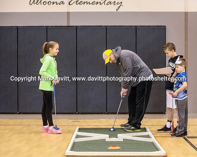 Patrick Wolfe lines up his putt under the watchful eyes of his children, Alea, Drew and Jack. The fourth annual 4th Altoona Elementary Golf in the Halls was held Jan. 28. Participants enjoyed a breakfast and  two, 18-hole mini-golf courses throughout the school's classrooms, hallways and gymnasiums.