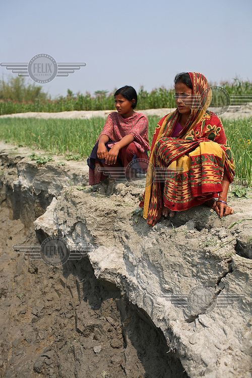 12 year old Arjina Khatun and her mother Asma Khatun lived in a house that was washed away by floods. Most of the 200 families on this embankment have moved two or three times because of erosion and some say they have had to move as many as 10 or 11 times during their lives. 'Chars' such as this - islands that are periodically submerged by the country's mighty rivers - are home to over five million people in Bangladesh. Life for the char dwellers is hazardous and uncertain. Flooding is common, as is loss of land and erosion, making it a struggle to grow enough food, and meaning families often need to relocate.