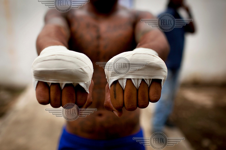 26 year old Chalernpol Sawansuk has his hands bandaged before a Mauy Thai bout. Sawansuk is serving a ten year sentence for drugs related offences. He was offered the chance to to participate in 'Prison Fight' a Mauy Thai competition at Khlong Phai prison. Mauy Thai has a long association with prisons and prisoners. Even its origin myths involve the incarcerated. It is said that in 1774 the Burmese king Hsinbyushin organised a series of fights between Thai prisoners, taken during the conquest of the Siamese capital of Ayutthaya seven years earlier, and Burmese champions. More recently the Thai prison system has embraced Mauy Thai as a form of rehabilitation. In 2012 an Estonian entrepreneur arranged bouts between Thai prisoners and Western Mauy Thai fighters under the banner 'Prison Fight'. For the prisoners a victory held the potential of time off their sentence. While the western fighters fought for a small purse and personal ambition.