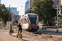 A pair of bike cyclists ride past the MetroRail train line in downtown Austin, Texas.