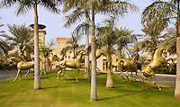 Dubai.  Al Qasr Hotel, luxury hotel built in the style of a Moroccan palace.  Gardens along the approach road to the hotel with lifesize sculptures of Arab thoroughbred horses.