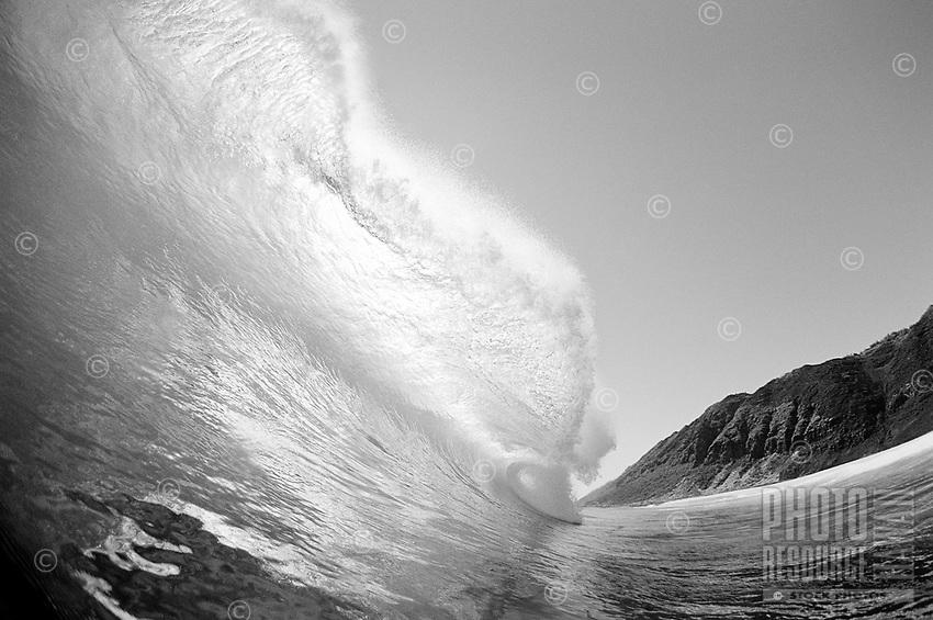 Backlit large wave breaking off the West Leeward side of O'ahu.