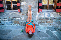 A woman lays on the ground looking at her phone charging outside the Turtmann Hut with legs up, relaxing after trail running during the Via Valais, a multi-day trail running tour connecting Verbier with Zermatt, Switzerland.