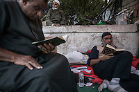 In this Wednesday, Jul. 10, 2013 photo, supporters of the ousted president Mohammed Morsi read a printed version of the Quran as they observe fasting before dusk in the streets nearby Al-Rabba Alawya mosque during the first day of the holy month of Ramadan in Cairo, Egypt. (Photo/Narciso Contreras).