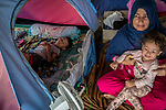 28 August 2019, Jakarta, Indonesia: - Zia Gil Mohammadi ,34, with daughter Mariam (2) and son Arush(5), from Afghanistan, at their camp in the grounds at the UNHCR refugee centre in Kalideres, Jakarta. Plans to re-locate the overcrowded refugees have been fast tracked after a fight broke out between the groups, many of whom have been in Indonesia for years waiting for placement. Tensions ran high between Afghan and African groups in the centre with a lack of adequate food for the refugees being the catalyst. The African groups, who were moved onto the footpath, were being bussed out today. Conditions in the centre are grim and the local Indonesian population not happy with the refugees presence in the suburb.Picture by Graham Crouch/The Australian