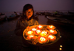 A sacred offering of candles set within marigold blossoms illuminates this young girl's face at dusk. While strolling along the Varanasi riverfront, I encountered her transporting the candles to the Ganges River. This offering to Ganga, the river god, is a long-held tradition in this ancient culture. The illumination of the girl's face provided a warm contrast to the cool, blue twilight. Once afloat, the cluster of candles disappeared into the gathering darkness.
