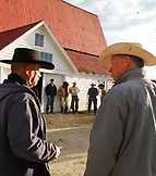 USA, Wyoming, Encampment, cowboys stand around talking before heading to brand cattle, Big Creek Ranch