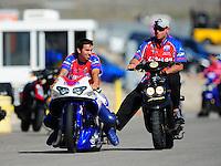 Oct. 29, 2011; Las Vegas, NV, USA: NHRA pro stock motorcycle rider Hector Arana Jr (left) with crew member during qualifying for the Big O Tires Nationals at The Strip at Las Vegas Motor Speedway. Mandatory Credit: Mark J. Rebilas-
