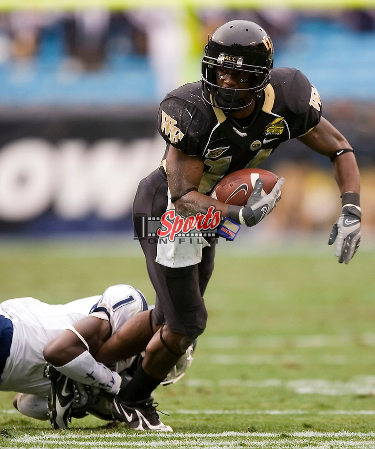 Wake Forest wide receiver Kevin Marion (14) tries to escape the grasp of Connecticut cornerback Darius Butler (1) during second half action of the Meineke Car Care Bowl Saturday, December 29, 2007 in Charlotte, NC.