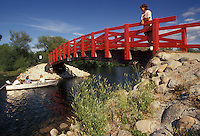 AJ2884, bridge, Minnesota, Woman standing on a red bridge which crosses over the Fish Hook River watching people cruise by in a boat in Park Rapids in the state of Minnesota.