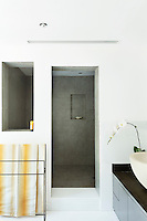 The minimalist bathroom features white walls and flooring and a walk-in, recessed shower room. A yellow striped towel hanging over a rail brings a touch of colour to the room.