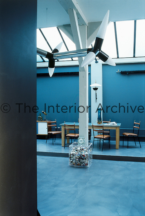 In the dining area a large luminos sculpture is suspended from the ceiling directly above a plexiglass box filled with a collection of matchboxes