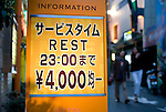 A couple walks past a sign advertising short stays from 4,000 yen outside a love hotel in the Dogenzaka entertainment district -- sometimes referred to as Love Hotel Hill -- in Tokyo, Japan on Sunday 19 April  2009. .Photographer: Robert Gilhooly
