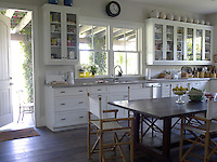 In the cool white kitchen a large rustic table is surrounded by director's chairs made of bamboo