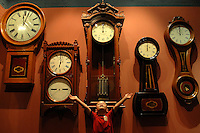 A young boy pretends to hold up a wall full of grandfather clocks and grandmother clocks at the North Carolina Transportation Museum in Spencer, NC.