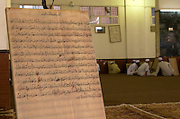 Zliten, Libya. Koranic Prayer Board in the Madrasa of Sidi Abdusalaam.  Students in the background study to memorize the Koran, working under the supervision of a teacher, or muqri.  This prayer board shows a number of mistakes which have been corrected by writing over the error.