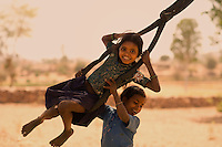Children playing on rustic swings made out of tyre tubes and hanging from a tree branch in a field.