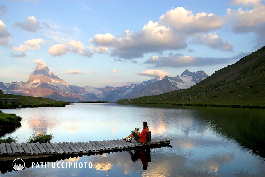 One woman on a dock in small lake watching the sunrise on the Matterhorn and the Swiss Alps