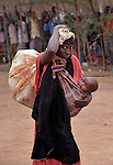 A baby on her side, a Somali refugee woman carries home food and other supplies she just received in the Dadaab refugee camp in northeastern Kenya.