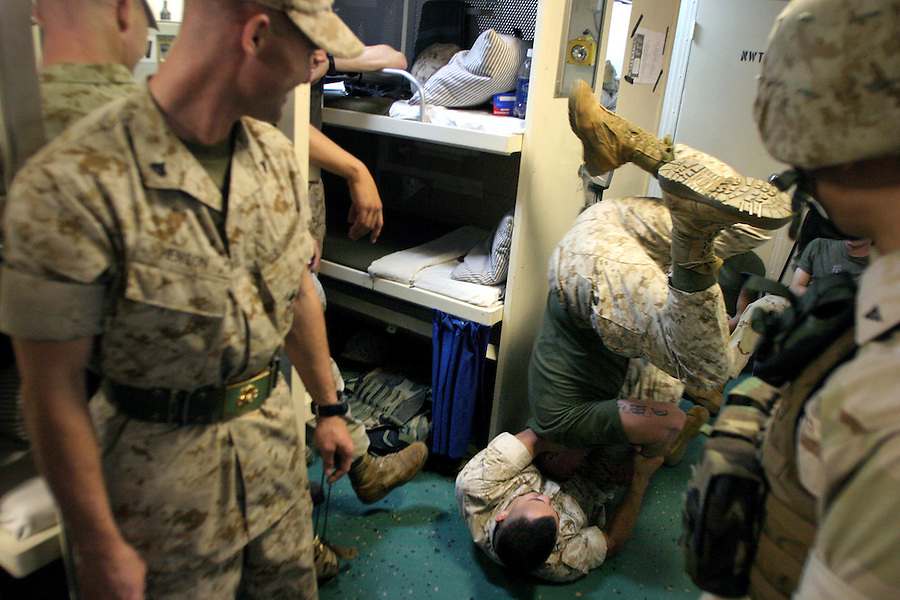 PFC Michael Burnison (on ground) and Lpcl. Adam Simpson (on head) (Scout-Sniper Platoon, H&S Co. 1/4 Marines) wrestle to pass the time in the berthings. Long hours fighting boredom aboard ship can lead to usual behavior among the Marines.