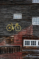 Yellow bike displayed on a barn  exterior facade, Vermont, USA.