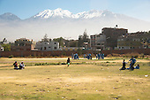 Arequipa, Peru. A. Antoniano (public elementary and secondary school). At recess time, children play on school grounds. Beyond the schoolyard is a residential neighborhood of Arequipa and, beyond that, is Nevado Chachani, a mountain that is also a volcano. No MR. ID: AL-peru.