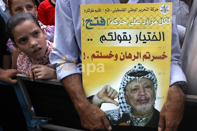 A Palestinian Fatah supporter holds a picture of former Palestinian leader Yasser Arafat during a protest marking the 48th anniversary of the Sabra and Shatila massacre in 1982, in the West Bank city of Nablus, September 16, 2014. The Sabra and Shatila massacre was the slaughter of between 762 and 3,500 civilians, mostly Palestinians and Lebanese Shiites, by the Kataeb Party, a Lebanese Christian militia, in the Sabra neighborhood and the adjacent Shatila refugee camp in Beirut, Lebanon. On 15 September, 63 Palestinian were individually identified and killed by an Israeli unit called Sayeret Matkal, and on 18 September 1982 a more widespread massacre was carried out by a Lebanese Christian Phalangist militia. Photo by Nedal Eshtayah