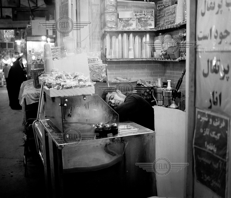 A man sleeps on the counter of his food stall.