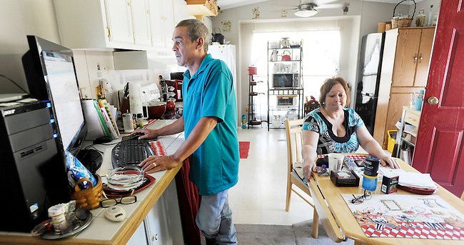 HOLD FOR STORY, ATTN:PATRICK SISON--Ricky Lesher, left, surfs the Internet while his wife Barbara Lesher, right, sits in the kitchen at their Lykens, Pa home Thursday, July 14, 2011.(AP Photo/Bradley C. Bower)