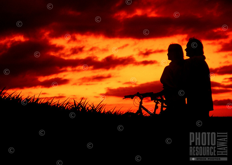 A couple on bicycles pause during their ride to watch a beautiful sunset