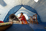 Puneshowari Shrestha picks up a sleeping pad as she organizes her tent in the morning in the village of Sanogoan, Nepal. People in this Newar community, hard hit by the April 2015 earthquake that ravaged Nepal, have been helped by the ACT Alliance to rebuild their lives. The ACT Alliance has provided a variety of services here since the quake, including blankets, tents, and livelihood assistance, and is helping villagers form the tens of thousands of cement blocks they will need to construct permanent housing.