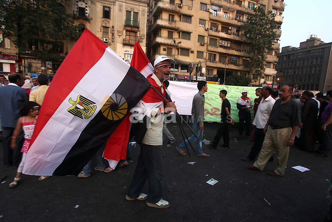 Egyptian protesters hold  national flag during a demonstration  against Egyptian presidential candidate Ahmed Shafiq in Tahrir Square decrying the result of the first round of voting in the Egyptian presidential election in Cairo, Egypt, Friday, June 1, 2012. Several hundred protesters rallied Friday in Cairo's Tahrir Square, the birthplace of the Egyptian uprising. Photo by Ashraf Amra