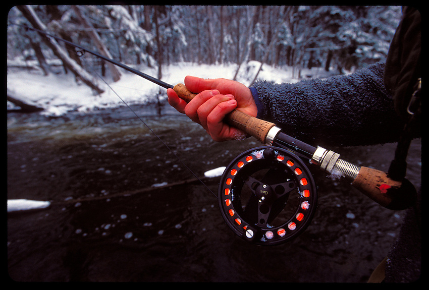 A MAN'S HAND SHOWS THE SIGNS OF COLD AS HE FLY FISHES FOR STEELHEAD ON THE CARP RIVER NEAR MARQUETTE, MICHIGAN FOLLOWING A SNOW STORM.