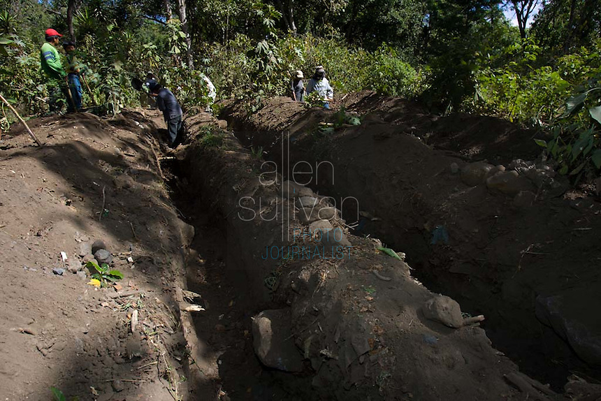 Workers dig trenches in an area of Panabaj, Guatemala on Wednesday, March 21, 2007 during a search for buried bodies. A deadly mudslide here was spawned by rains associated with Hurricane Stan in October 2005. Initially, up to 500 Tzujutil Maya villagers were believed to have been killed by the mudslide, which essentially  wiped away the town. Forensic anthropologists from the Fundación de Antropología Forense de Guatemala have been working to unearth the bodies of the missing and have recovered more than 100. They have also found the number of missing to be lower than originally thought, after many people were located in shelters or living in other towns after the disaster.