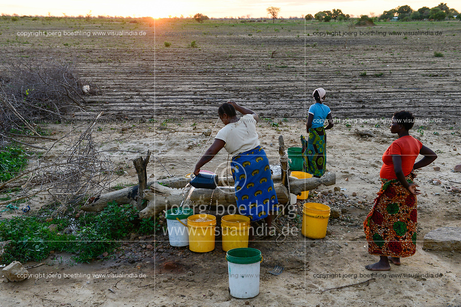 ZAMBIA, Mazabuka, Chikankata area, medium scale farmer Stephen Chinyama, homestead, women fetch water from well at dusk