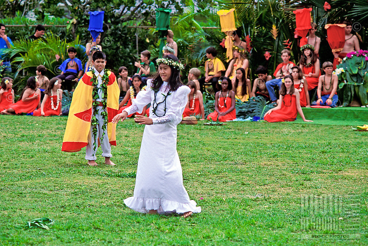 A young local girl wearing a white holoku (traditional dress) and haku lei (floral headpiece) dances hula at the May Day celebration, Aikahi Elementary School, Kailua, Oahu. A young boy wearing a traditional yellow and red cape stands nearby and sev