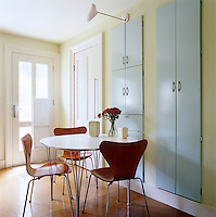 1950's style built-in cupboards dominate a wall of the kitchen beside a small breakfast area
