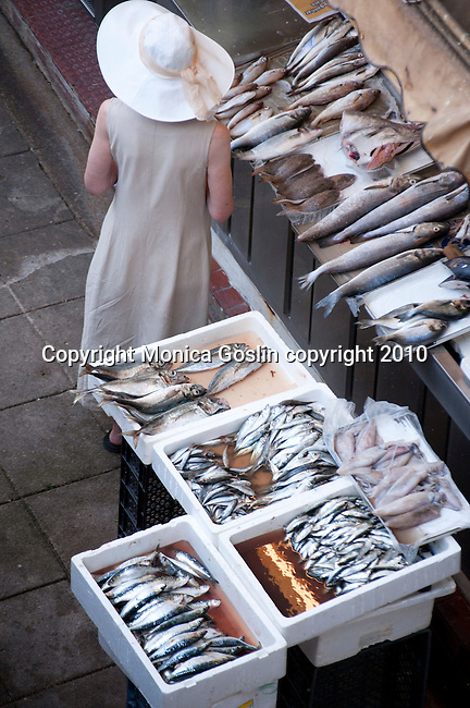 A woman in a large white hat gets fish at the Mercado do Bolhao in Porto, Portugal.